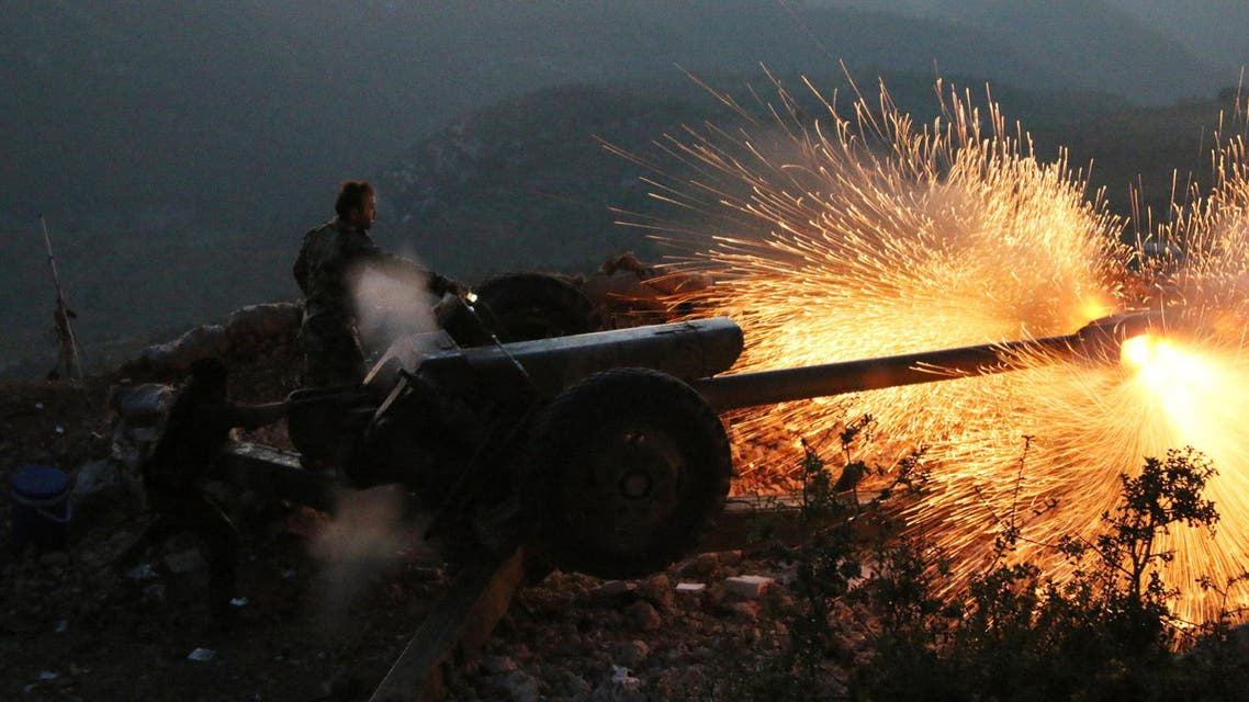 In this photo taken on Saturday, Oct. 10, 2015, Syrian army personnel fire a cannon in Latakia province, about 12 from the border with Turkey in Syria.  AP