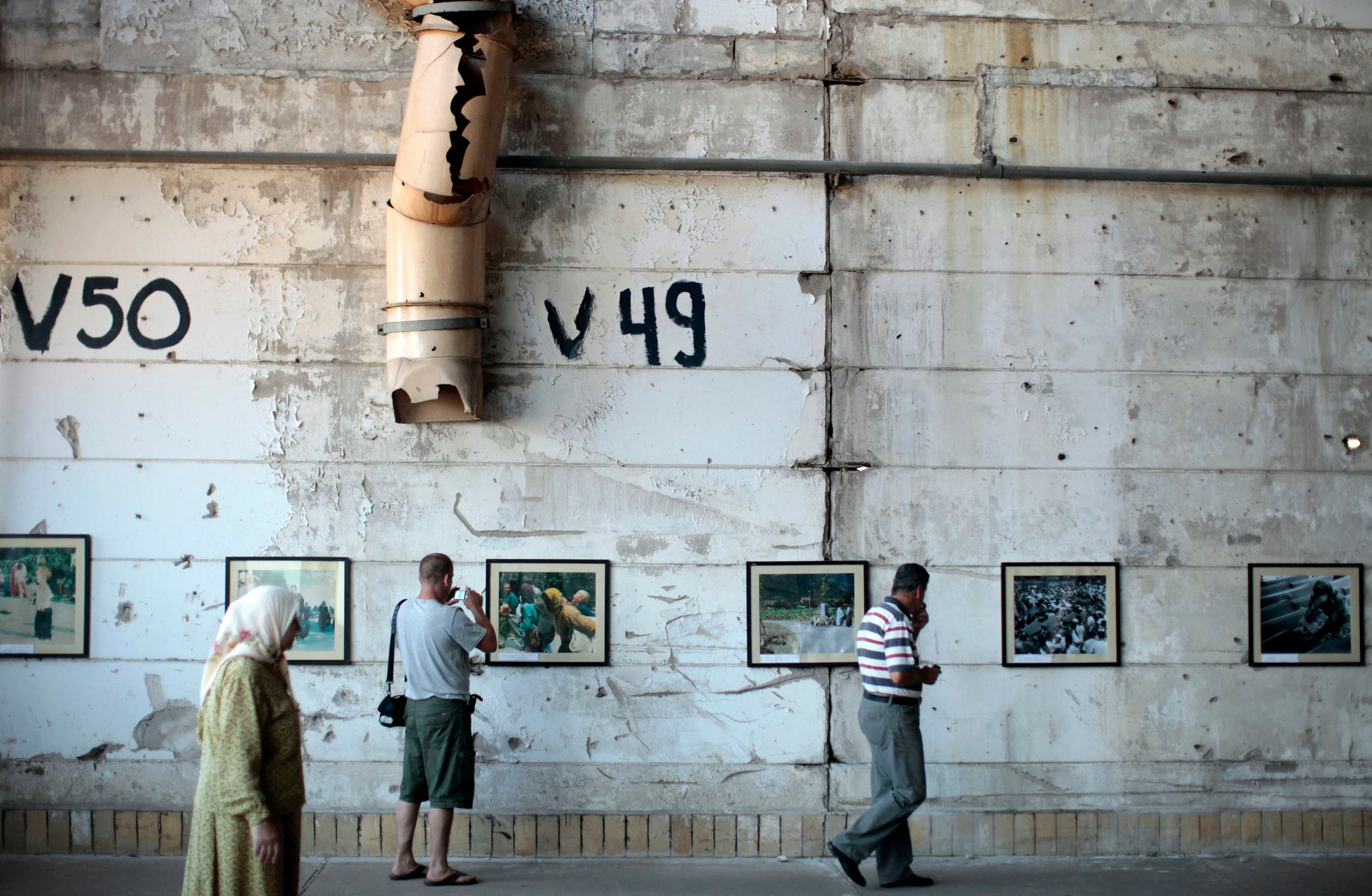 People look at pictures of before and after the war in the Memorial Room Museum in Potocari, near Srebrenica July 3, 2011. (Reuters)