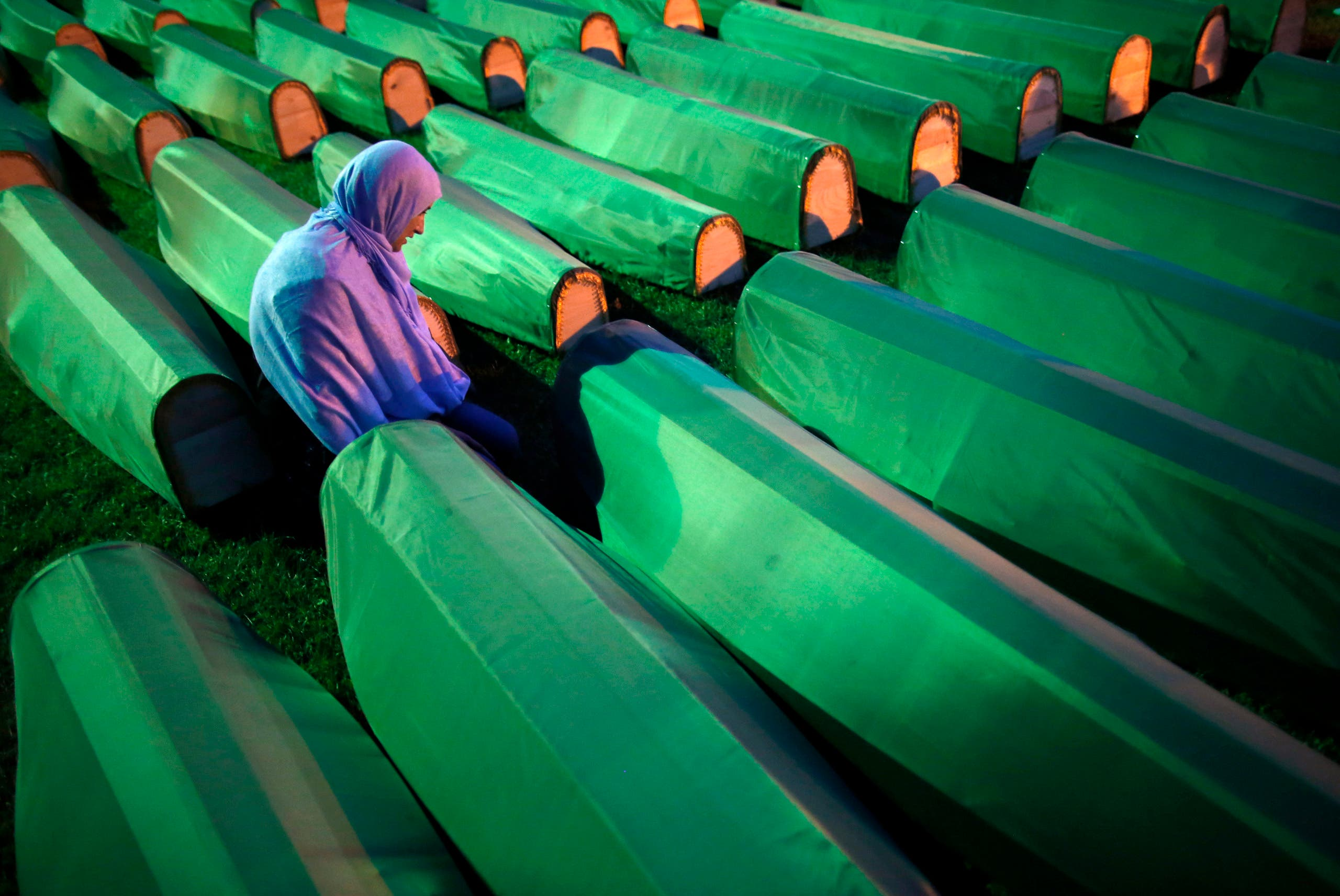 A Bosnian Muslim kneels near the coffin of a relative before a mass funeral for bodies found in a mass grave, in Kozarac, near Prijedor, July 19, 2014. (Reuters)