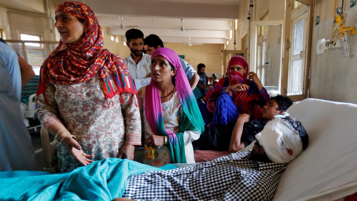 Family members stand beside an injured man as he lies in a hospital bed after clashes between Indian police and protesters, in Srinagar. (Reuters)