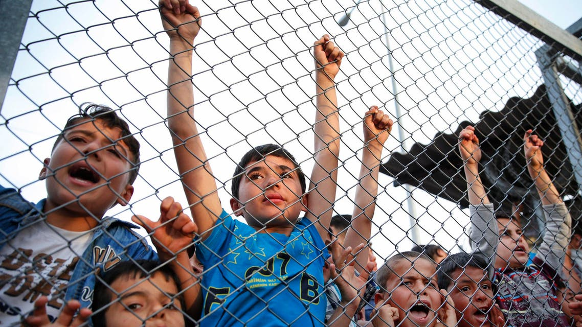 Syrian refugee children chant slogans behind a fence at the Nizip refugee camp in Gaziantep province, southeastern Turkey, following a visit by German Chancellor Angela Merkel and top European Union officials, Saturday, April 23, 2016. (AP)