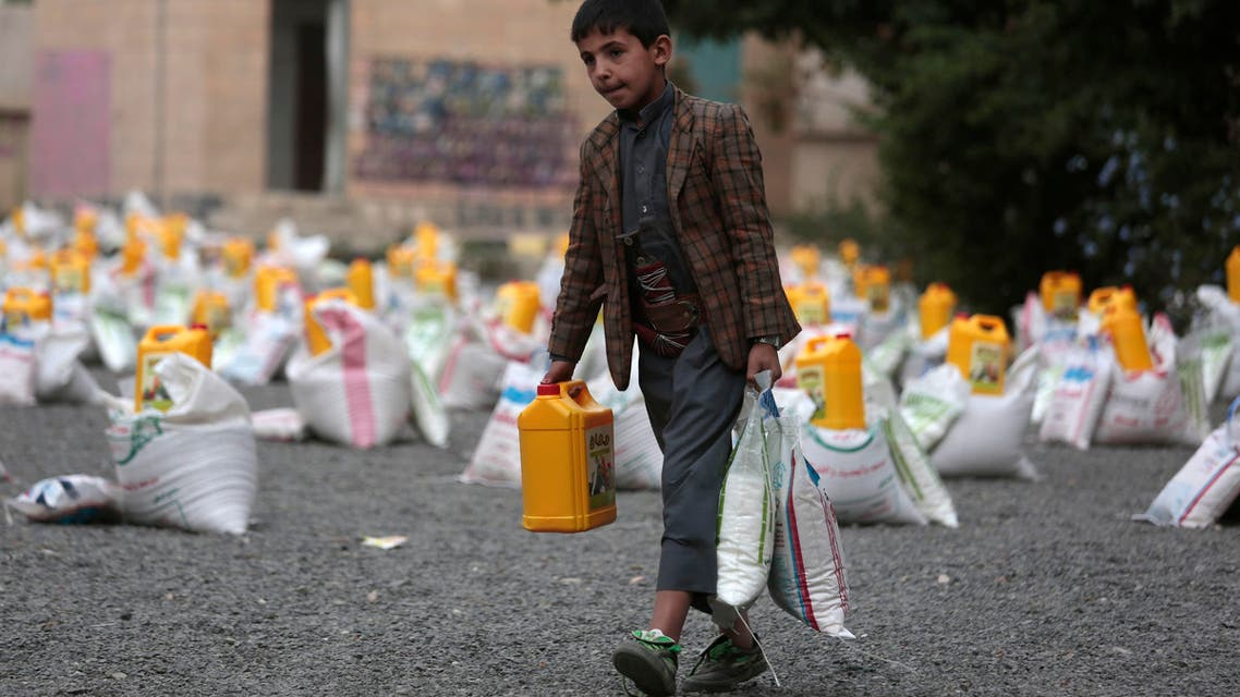 A boy carries food supplies provided by a local charity to conflict-affected Yemenis in Sanaa. (File:AP)