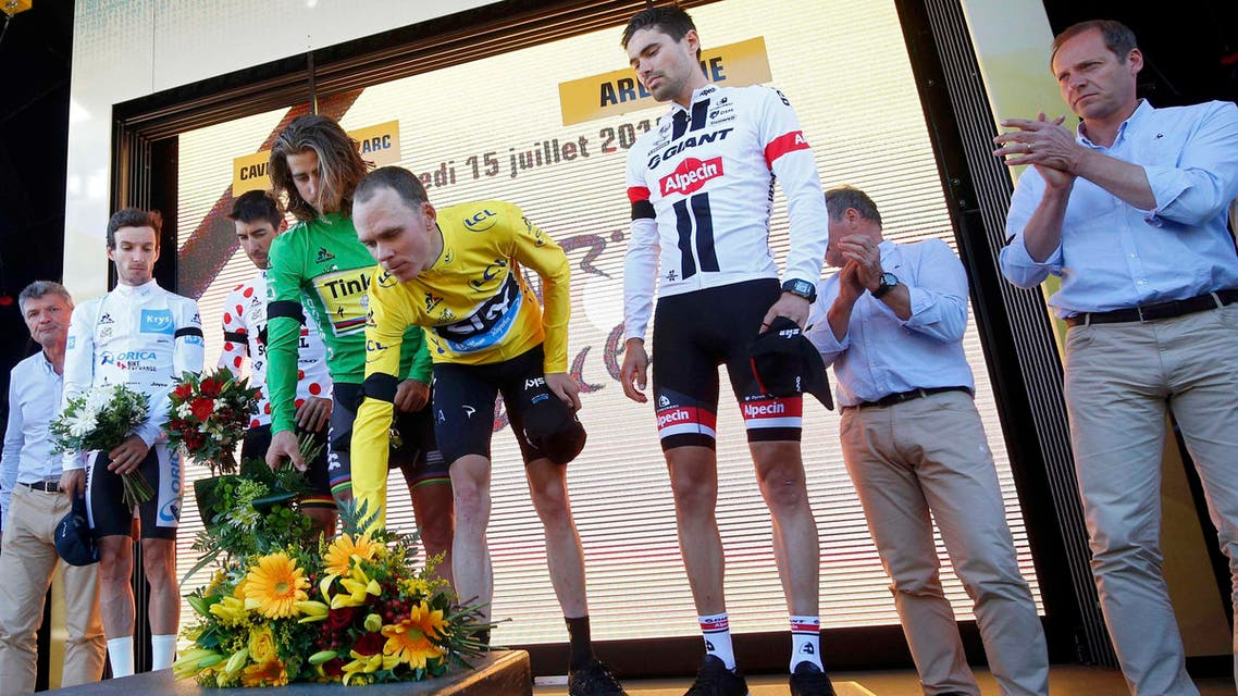 iders and officials of the Tour de France lay flowers after observing a minute of silence to commemorate victims of Nice truck attack on Bastille Day. REUTERS