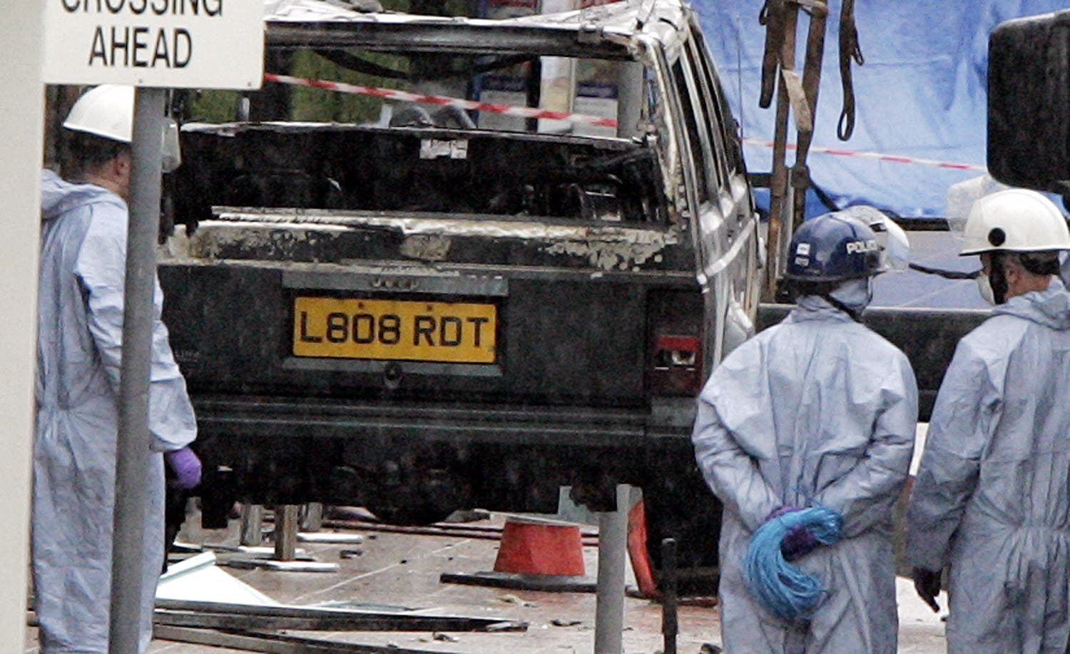Police forensics view the remain's of the burnt out jeep being lifted from the scene at Glasgow International Airport, 01 July 2007 where a Jeep Cherokee rammed and burst into flames in a terror attack at Scotland's Glasgow Airport. (AFP)