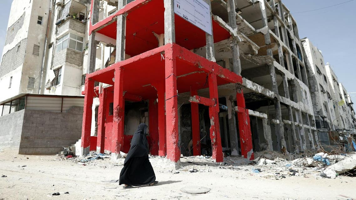 A Palestinian veiled woman walks past a building which was destroyed during the 50-day war between Israel and Hamas-led militants in the summer of 2014, in the northern Gaza Strip city of Beit Hanun, on May 9, 2016.  THOMAS COEX / AFP