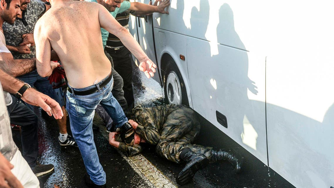 People beat a soldier up on the ground after taking over a military position on the Bosphorus bridge in Istanbul on July 16, 2016. (AFP)