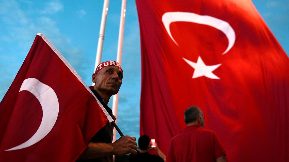 A Pro-Erdogan supporter holds a Turkish national flag as he looks on during a rally at Taksim square in Istanbul. (AFP)