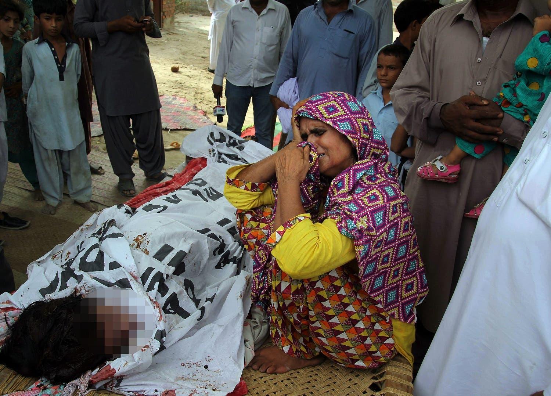 Anwar Bibi, the mother of of slain model Qandeel Baloch mourns beside her body at her home, in Shah Sadar Din village, near Dera Ghazi Khan, Pakistan. (AP)