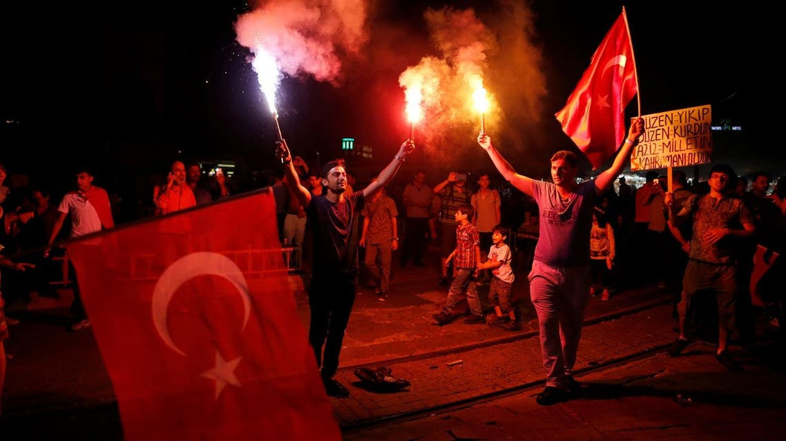 Supporters of Turkish President Tayyip Erdogan light up flares and wave Turkish national flags during a pro-government demonstration on Taksim square in Istanbul. (Reuters)