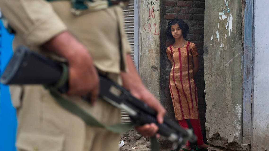 In this Sunday, July 17, 2016 photo, a Kashmiri girl watches an Indian paramilitary soldier standing guard during curfew in Srinagar. (AP)