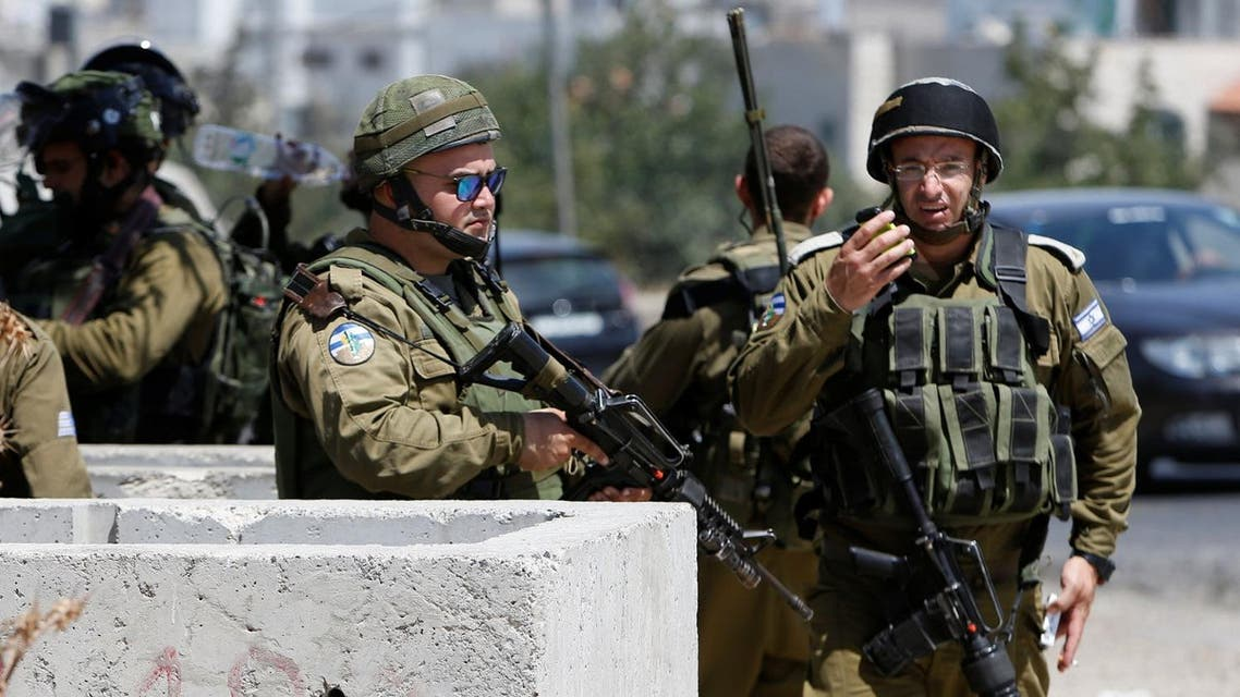 Israeli soldiers gather at scene of a stabbing attack near Arroub refugee camp near the West Bank city of Hebron July 18, 2016. REUTERS/Mussa Qawasma