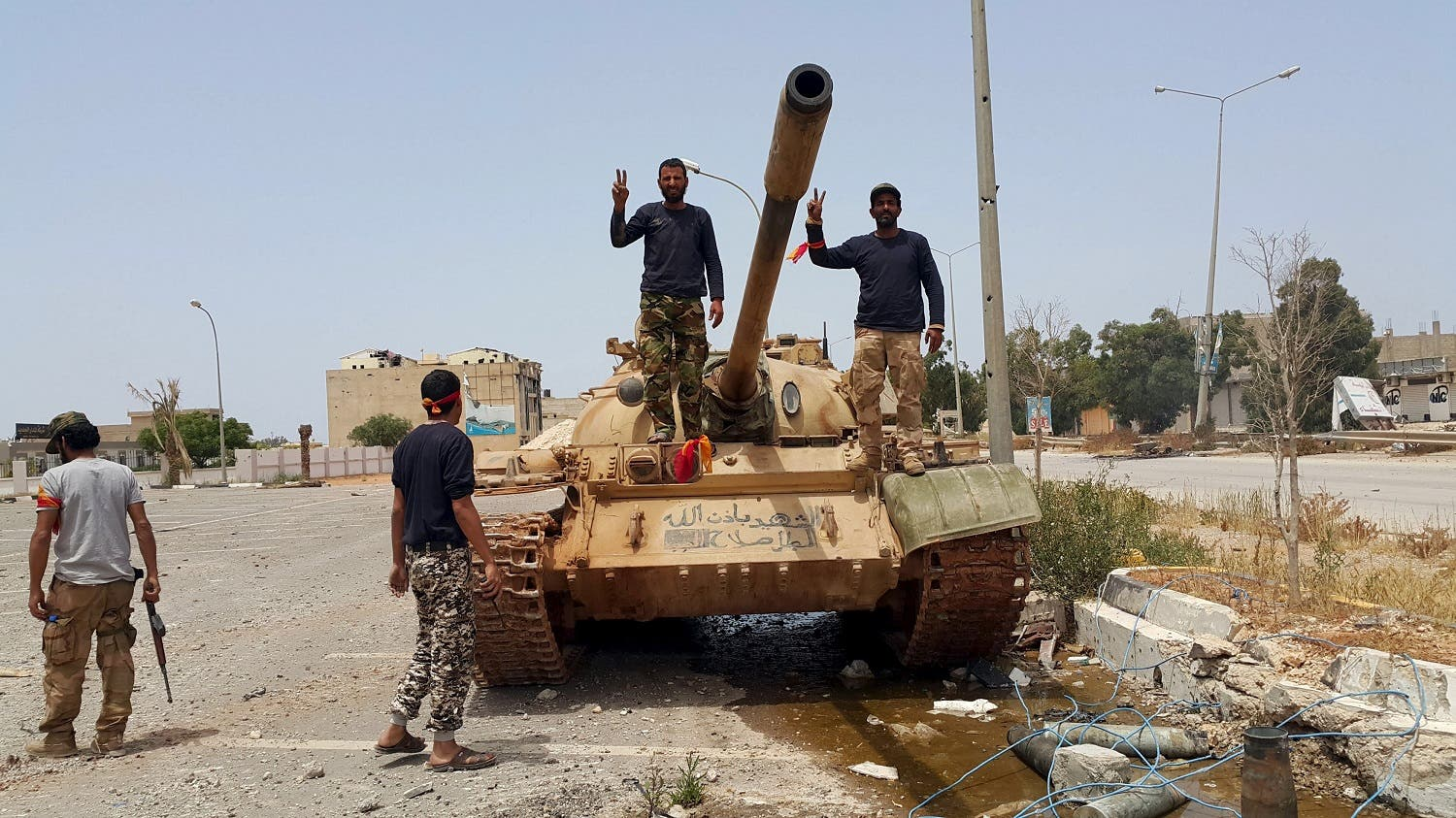 Members of the Libyan pro-government forces gesture as they stand on a tank in Benghazi, Libya, May 21, 2015. (Reuters)