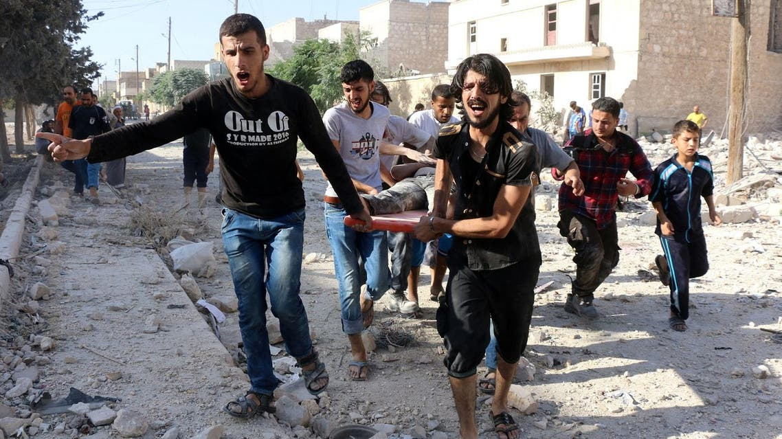 Syrians carry a stretcher as they evacuate victims from the rubble of a collapsed building following a reported air strike on the rebel-held neighbourhood of Sakhur in the northern city of Aleppo. (AFP)