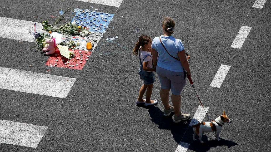 A woman and a child stand near a makeshift memorial placed on the road during a minute of silence on the third day of national mourning to pay tribute to victims of the truck attack along the Promenade des Anglais in Nice. (Reuters)
