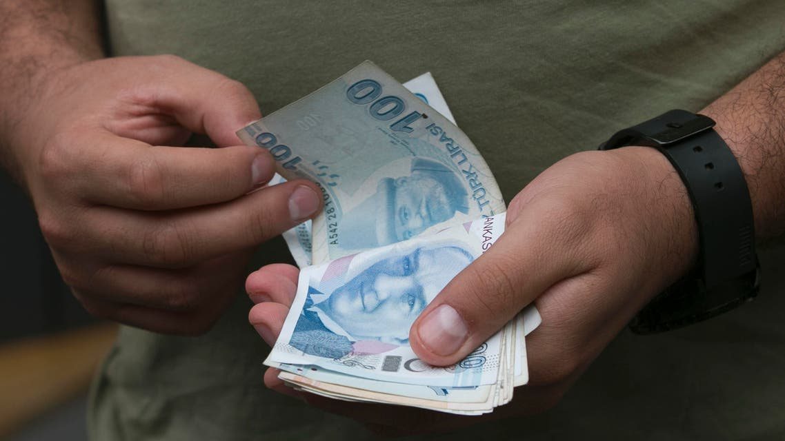 A man counts his Turkish liras as he leaves from a currency shop in central Istanbul Wednesday, July, 20, 2016.Turkey's central bank has cut a key interest rate to help shore up the economy, days after an attempted coup. Turkish stocks are way down from pre-coup levels, as is the Turkish lira.(AP Photo/Petros Giannakouris)