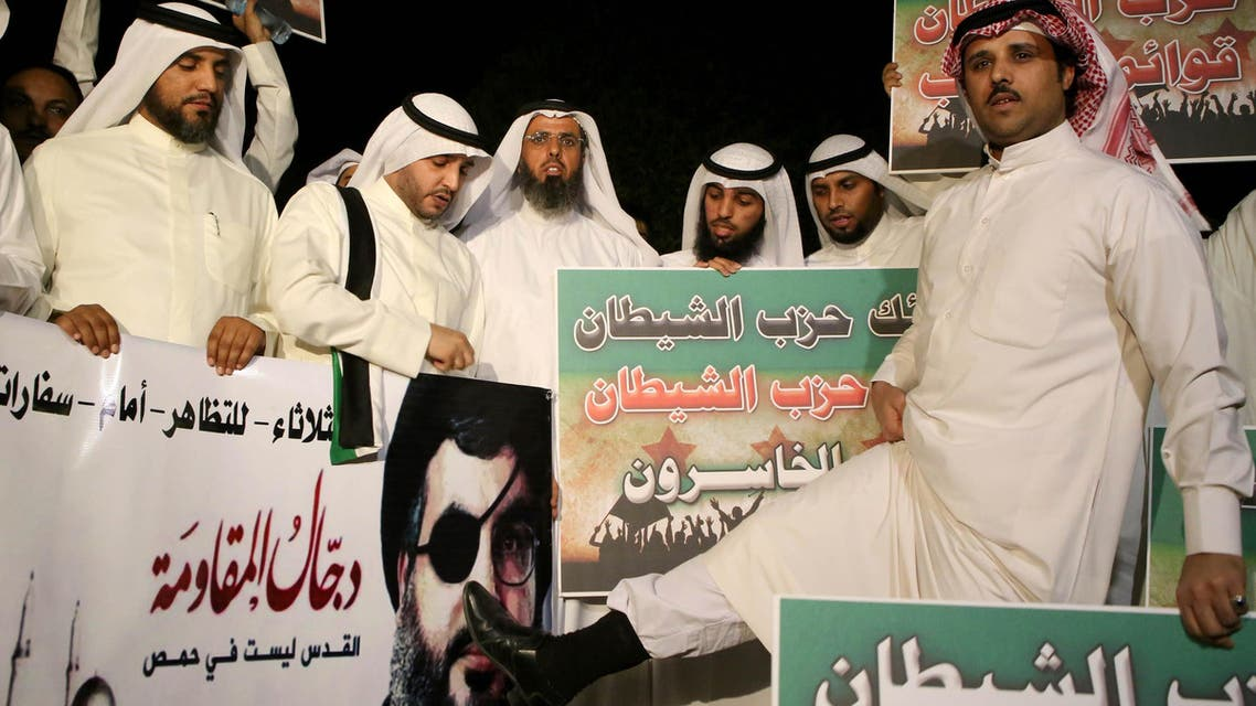 Kuwaiti protesters hold placards against Lebanese Shiite movement Hezbollah's chief Hassan Nasrallah (portrait) during a protest in front the Lebanese embassy against Hezbollah's and Iran's involvement in Syria, in Kuwait city on June 11,2013. AFP