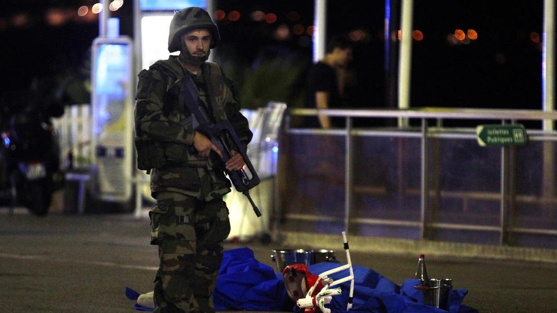 A soldier stands next to a dead body covered with a blue sheet on the Promenade des Anglais seafront in the French Riviera town of Nice. (File photo: AFP)