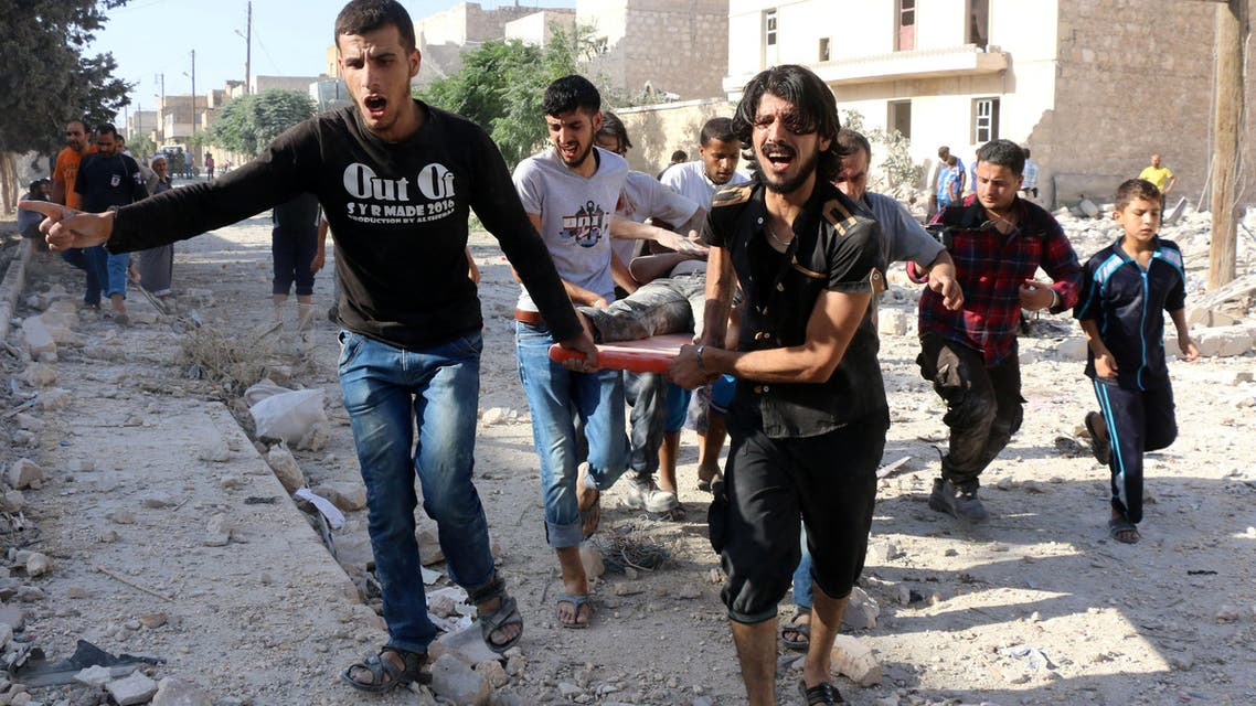 Syrians carry a stretcher as they evacuate victims from the rubble of a collapsed building following a reported air strike on the rebel-held neighborhood of Sakhur in Aleppo on July 19, 2016. (AFP)