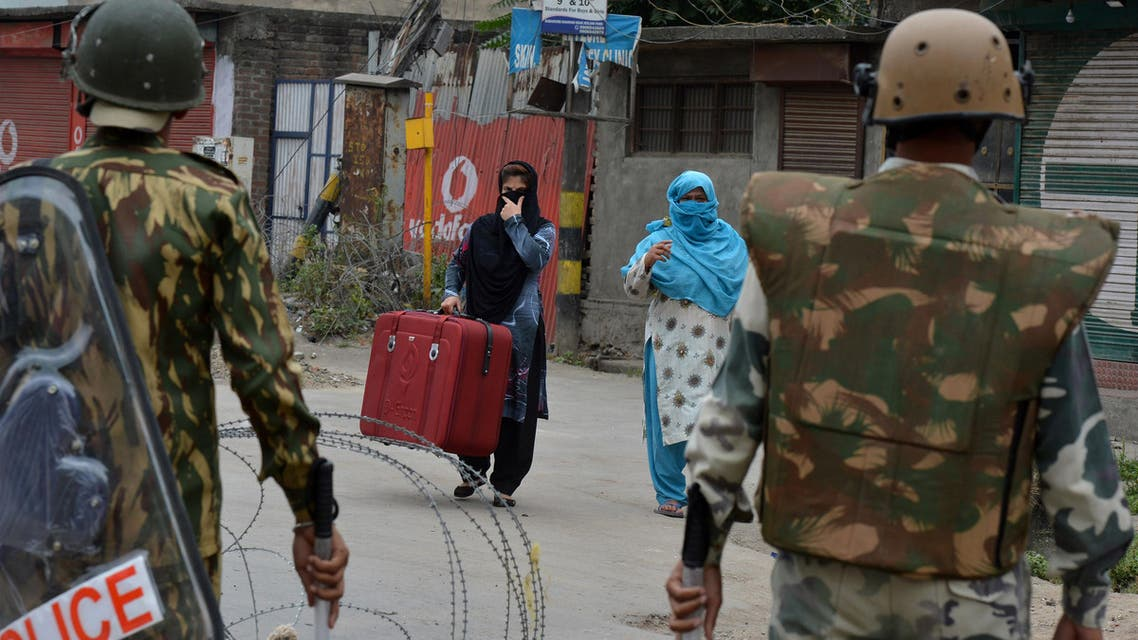 Indian paramilitary troopers stand guard as Kashmiri women approach them on the 14th day of a curfew in downtown Srinagar on July 22, 2016. (AFP)
