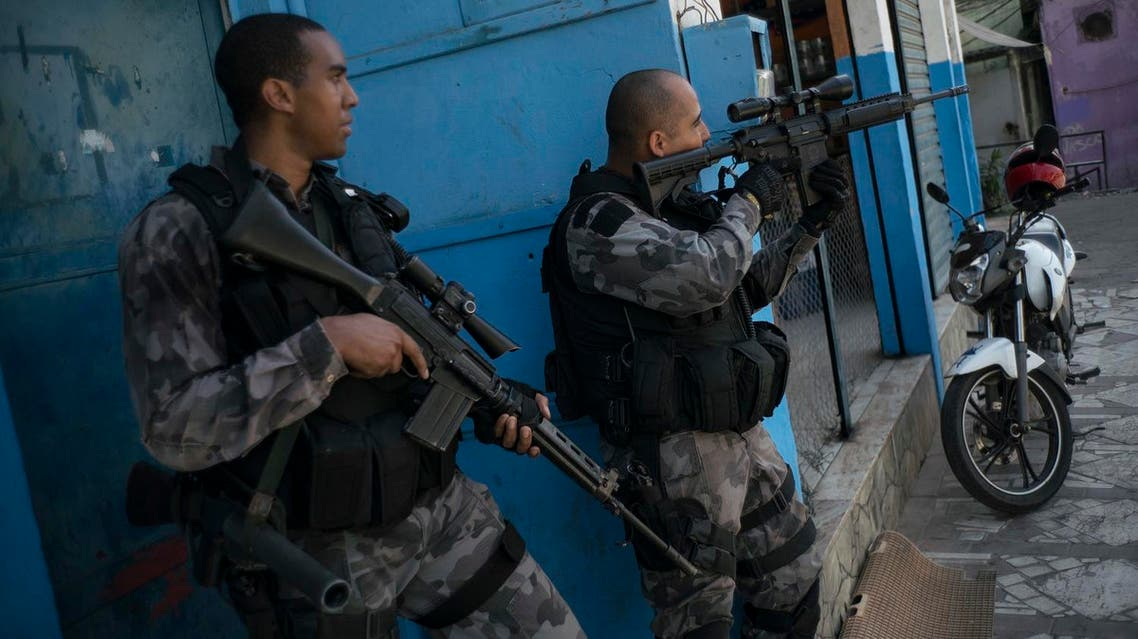 Officers take positions during a police operation against drug traffickers at the Jacarezinho slum in Rio de Janeiro, Brazil, Wednesday, June 29, 2016. Recent violence is adding to worries about safety in Rio during the Olympics. Officials have warned that budget shortfalls may compromise security during the games. (AP)