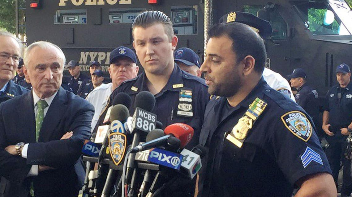 """In this photo provided by the New York Police Department (NYPD), Sgt. Hameed Armani, right, and Officer Peter Cybulski talk at a news conference, Thursday, July 21, 2016 at Columbus Circle in New York, about the hoax bomb that was tossed into their police van the night before in Times Square. Police Commissioner William Bratton, left, said, """"These two officers are heroes of the NYPD, heroes of New York City."""" A suspect was taken into custody Thursday. (NYPD via AP )"""