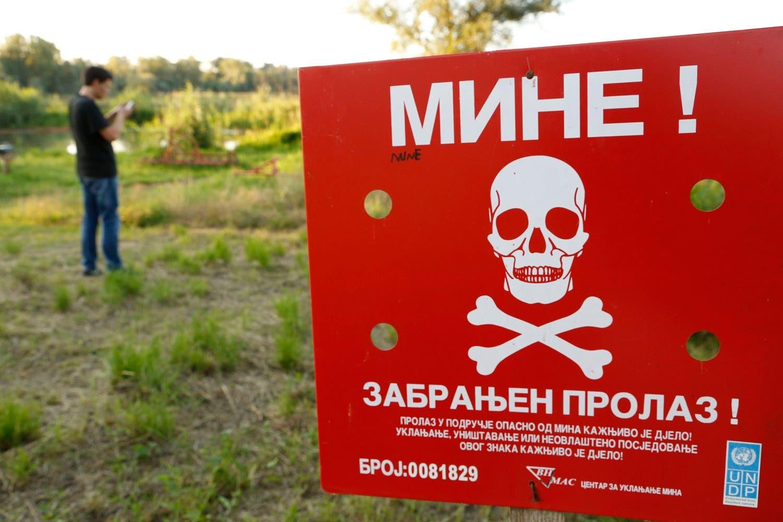 A Bosnian man plays Pokémon Go on his phone in a minefield near the Bosnian town of Brcko. (AP)