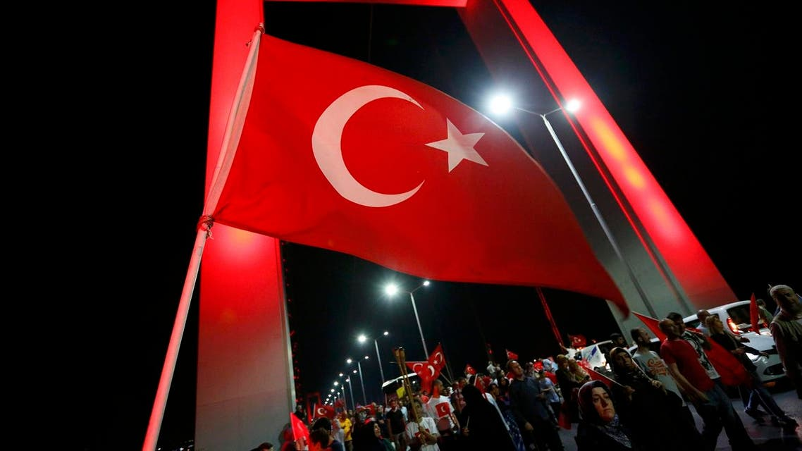 A Turkish national flag waves as pro-government demonstrators march over the Bosphorus Bridge, from the Asian to the European side of Istanbul, Turkey, July 21, 2016. REUTERS