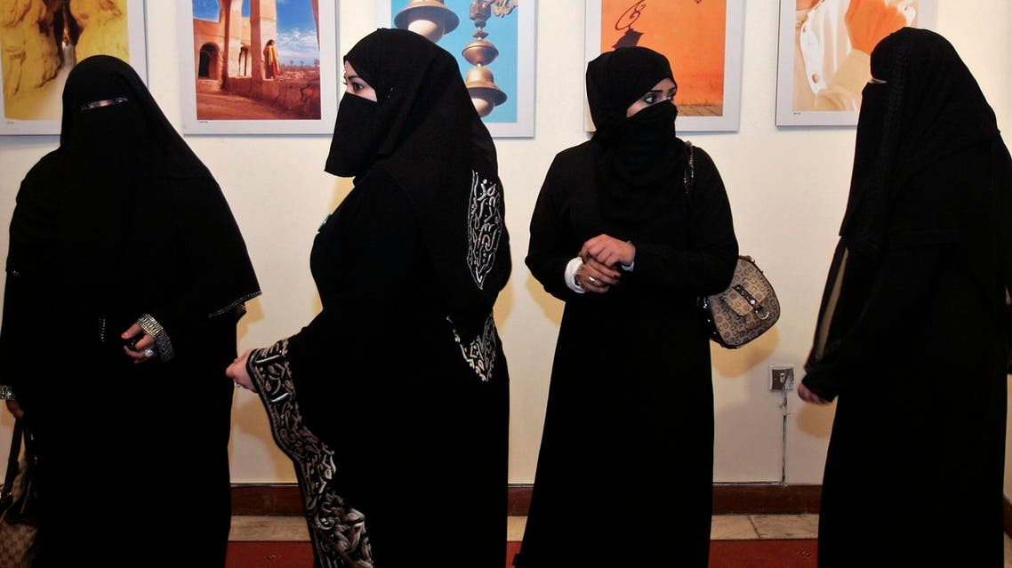 A group of Saudi women look at photographs by a group of Saudi women photographers during the opening of their gallery in Amman April 8, 2009. REUTERS