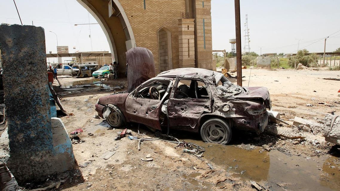 A destroyed vehicle is seen at the site of a suicide bomb attack at a checkpoint in Rashidiya, a district north of Baghdad, Iraq July 13, 2016. REUTERS