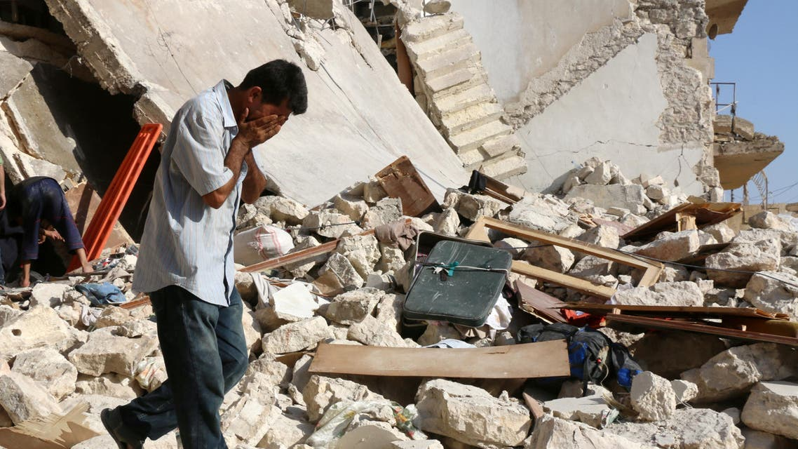 A Syrian man reacts as rescuers look for victims under the rubble of a collapsed building following a reported air strike on the rebel-held neighbourhood of Sakhur in the northern city of Aleppo on July 19, 2016. (AFP)