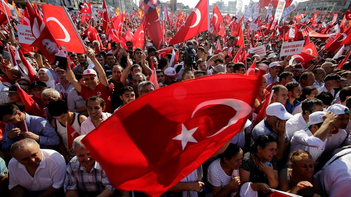 A supporter of the Republican People's Party, or CHP, waves a Turkish flag bearing a portrait of Mustafa Kemal Ataturk, the founder of modern Turkey, during a 'Republic and Democracy Rally' at Taksim square in central Istanbul, Sunday, July 24, 2016. Thousands of supporters of Turkey's main opposition group and some ruling party members rallied in Istanbul to denounce a July 15 coup attempt, a rare show of political unity that belied opposition unease over President Recep Tayyip Erdogan's crackdown since the failed uprising. (AP Photo/Petros Karadjias)