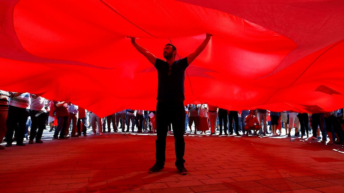 A man stands under the giant Turkey's national flag as supporters of various political parties gather in Istanbul's Taksim Square. (Reuters)