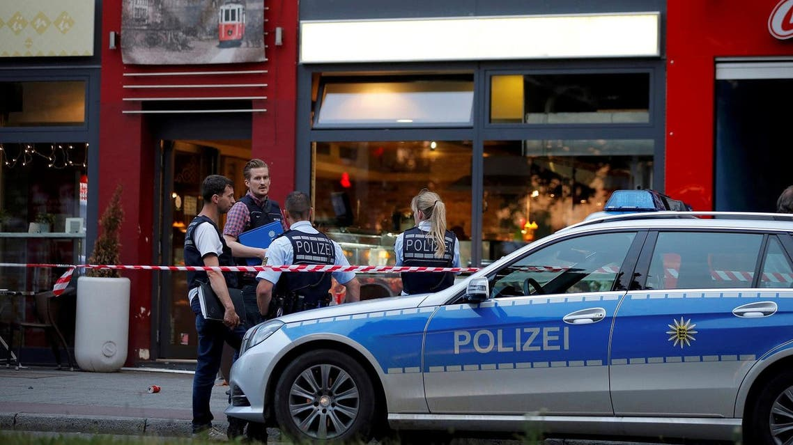 Police stand outside where a 21-year-old Syrian refugee killed a woman with a machete and injured two other people in the city of Reutlingen, Germany July 24, 2016