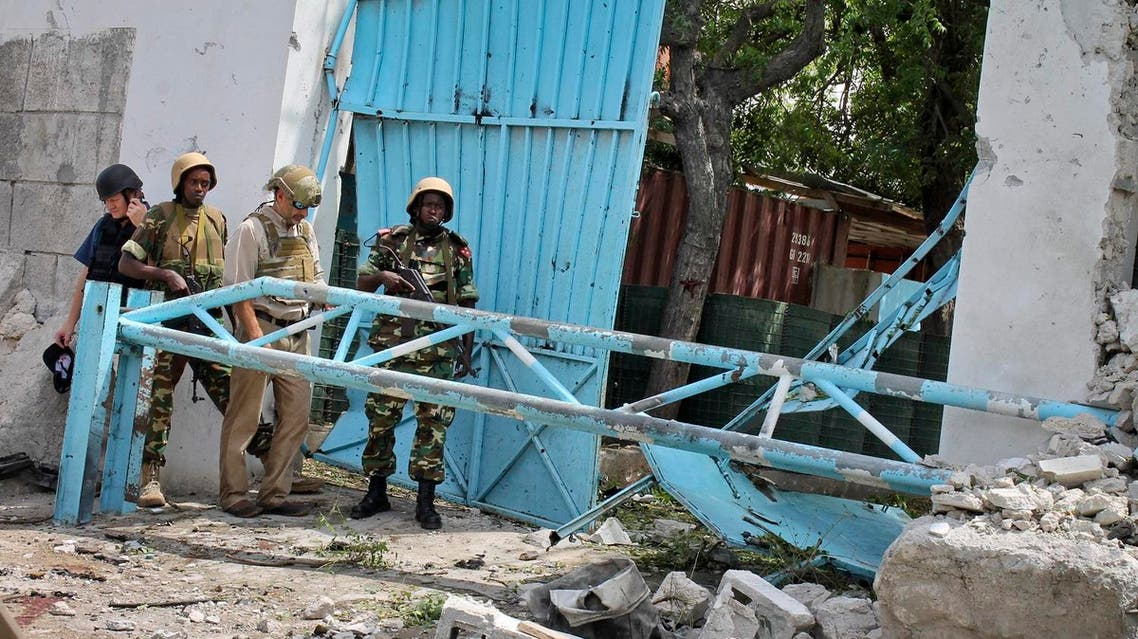 African Union peacekeepers and unidentified foreigners stand outside the main U.N. compound, following an attack on it in Mogadishu, Somalia Wednesday, June 19, 2013. Al-Qaida-linked militants detonated multiple bomb blasts and engaged in ongoing battles with security forces in an attempt to breach the main U.N. compound in Mogadishu, officials said Wednesday. (AP)