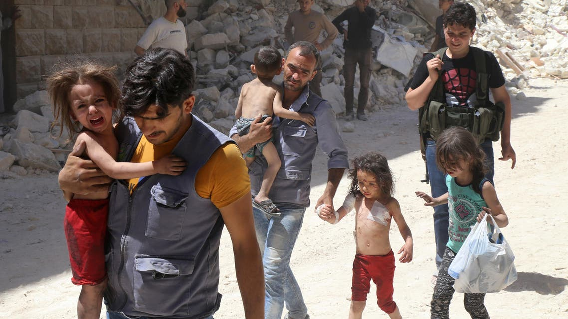 Syrian men carry injured children amid the rubble of destroyed buildings following reported air strikes on the rebel-held neighbourhood of Al-Mashhad in the northern city of Aleppo, on July 25, 2016.  (AFP)