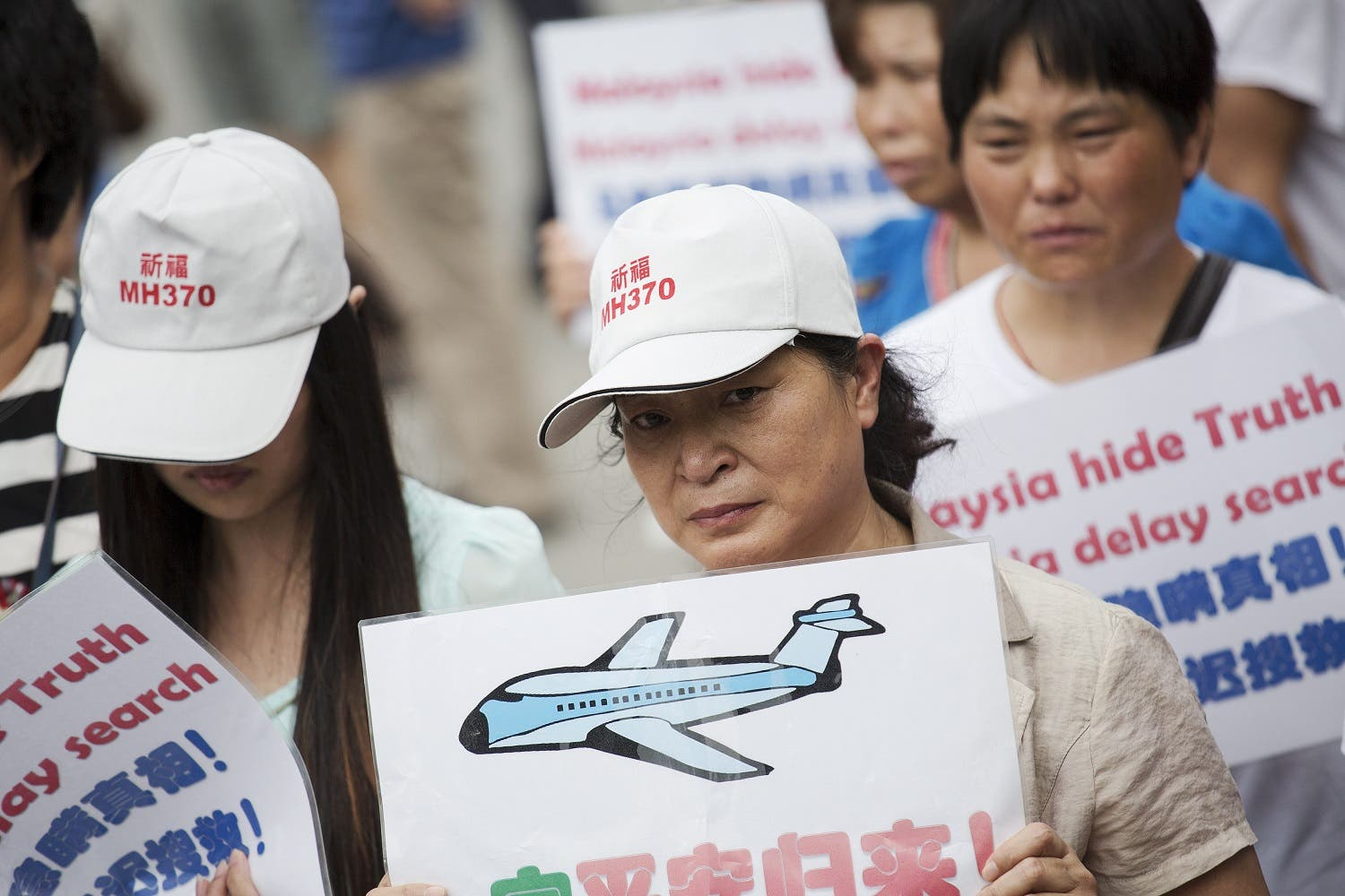 People whose relatives were aboard Malaysia Airlines flight MH370 hold placards as they protest near the Malaysian embassy in Beijing August 7, 2015. Angry relatives of Chinese passengers aboard a Malaysia Airlines plane missing for more than a year clashed with police in Beijing on Friday as French officials extended the search for debris on remote Indian Ocean island beaches. REUTERS/Damir Sagolj