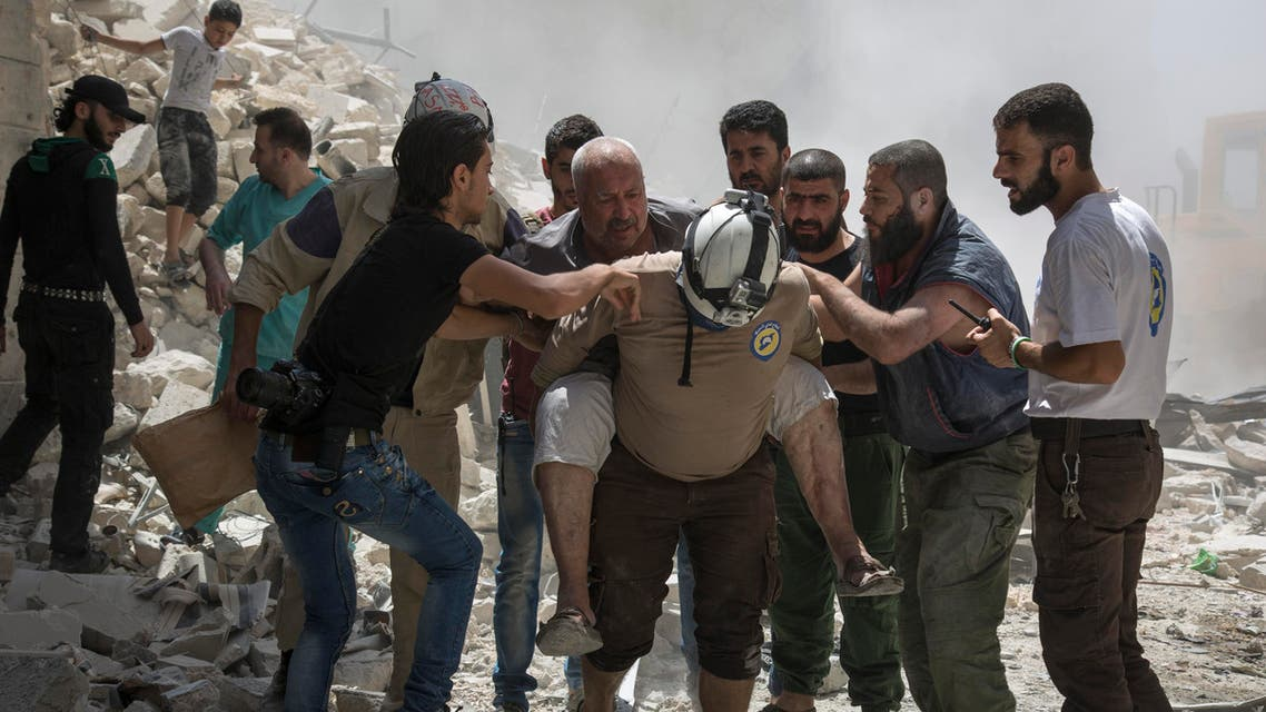 Syrians carry a wounded man away from the rubble of a building that according to the Syrian Observatory for Human Rights was destroyed during a barrel bomb attack by government forces near Aleppo on July 26, 2016. (AFP)