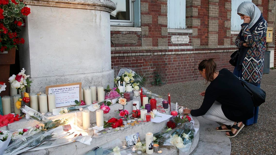 Women gather near flowers and candles at the town hall in Saint-Etienne-du-Rouvray, near Rouen in Normandy, France, to pay tribute to French priest, Father Jacques Hamel, who was killed with a knife and another hostage seriously wounded in an attack on a church that was carried out by assailants linked to ISIS, July 26, 2016. (Reuters)