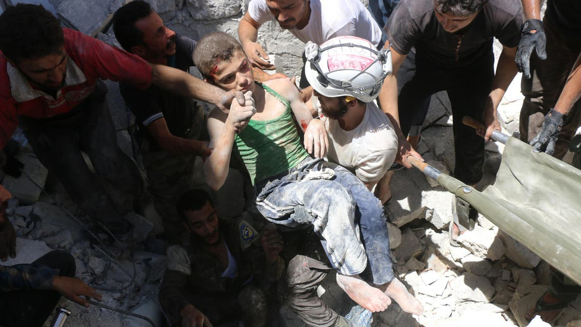 وهم ينتشلون طفلاً من تحت الأنقاض في حلب - فرانس برس