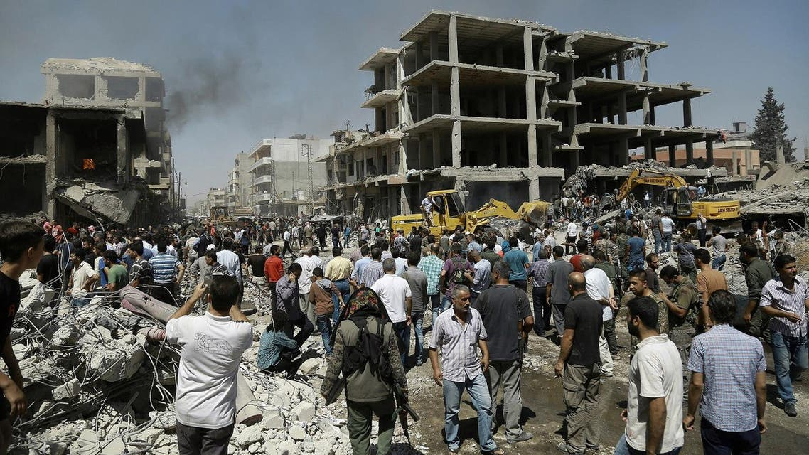 Syrians gather at the site of a bomb attack in Syria's northeastern city of Qamishli on July 27, 2016. (AFP)