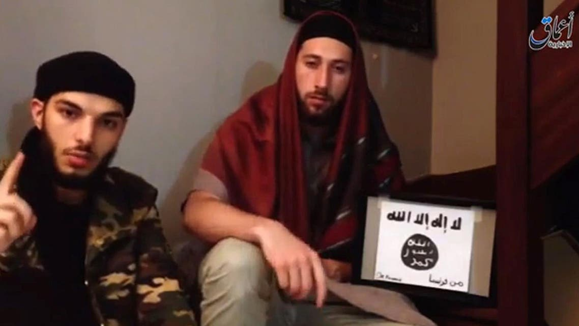 An image grab taken the video shows the two men who identify themselves as 'Abu Jaleel al-Hanafi'(L) and 'Ibn Omar' (R) sitting next to the logo of ISIS while pledging allegiance to Abu Bakr al-Baghdadi. afp