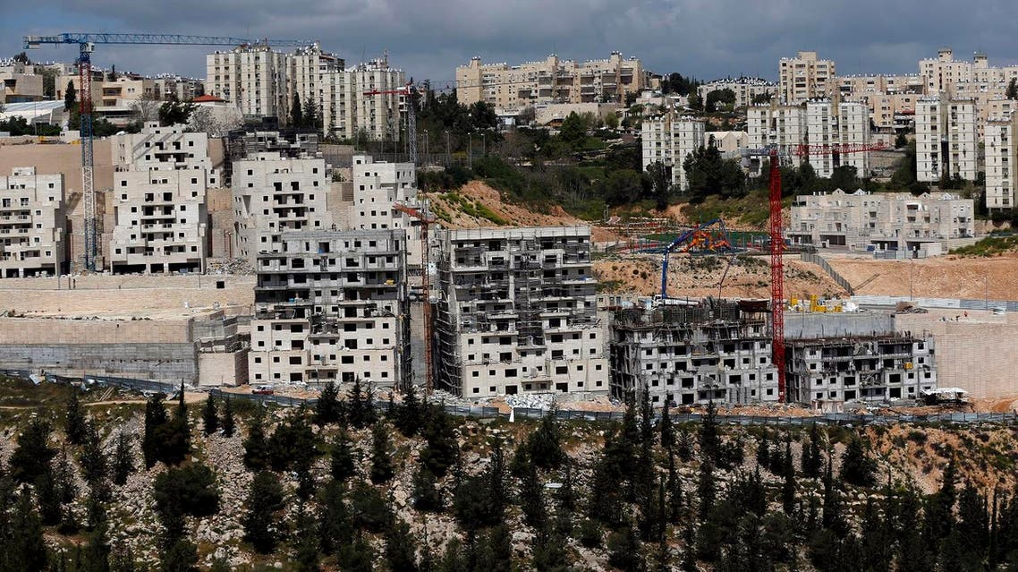 A general view taken on March 29, 2016 shows Israeli construction cranes and excavators at a building site of new housing units in the Jewish settlement of Neve Yaakov, in the northern area of east Jerusalem.  AHMAD GHARABLI / AFP