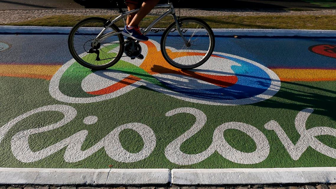 A woman rides her bicycle as she passes over a newly-painted bicyle lane ahead of the Rio 2016 Olympic games near Barra da Tijuca beach in Rio de Janeiro, Brazil, July 27, 2016. REUTERS/