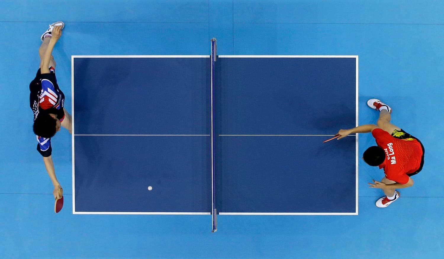 Ma Long of China competes against Ryu Seungmin of South Korea, left, in the men's team table tennis gold medal match at the 2012 Summer Olympics, Wednesday, Aug. 8, 2012, in London. (AP)