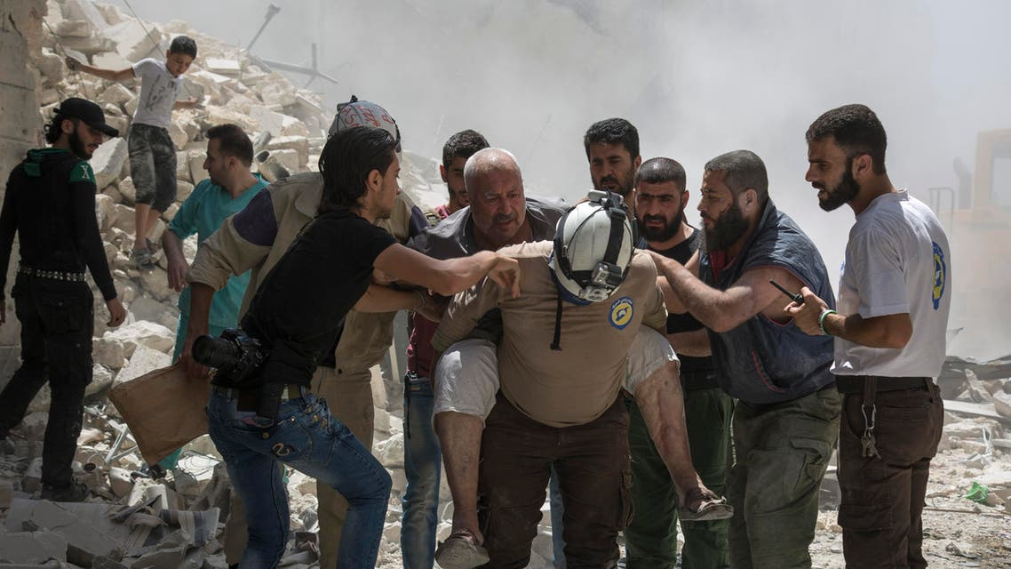 Syrians carry a wounded man away from the rubble of a building that according to the Syrian Observatory for Human Rights was destroyed during a barrel bomb attack by government forces in the opposition-held district of Al-Mashhad near Aleppo on July 26, 2016. Syrian government forces seized a rebel-held neighbourhood on the northwest outskirts of Aleppo, tightening their siege of the opposition-controlled parts of the city, a monitor said. (AFP)