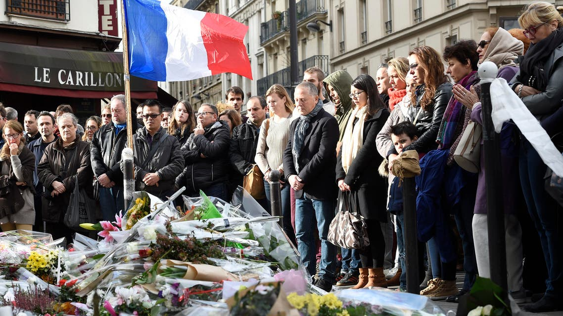 "People observe a minute of silence on November 16, 2015 at the Le Carillon cafe at the corner of Rue Bichat and Alibert in the 10th arrondissement and ""Le petit Cambodge"" restaurant at the site of the attacks in Paris, to pay tribute to victims of the attacks claimed by Islamic State which killed at least 129 people and left more than 350 injured on November 13. AFP PHOTO / ERIC FEFERBERG"