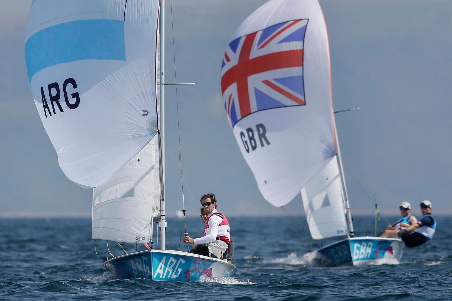 Argentina's Lucas Calabrese and Juan de la Fuente, foreground, and Great Britain's Luke Patience and Stuart Bithell compete during the 470 men's class medal race at the London 2012 Summer Olympics, Friday, Aug. 10, 2012, in Weymouth and Portland, England. Australia's Mathew Belcher and Malcolm Page won the gold medal, Great Britain's won the silver and Argentina's won the bronze. (AP)