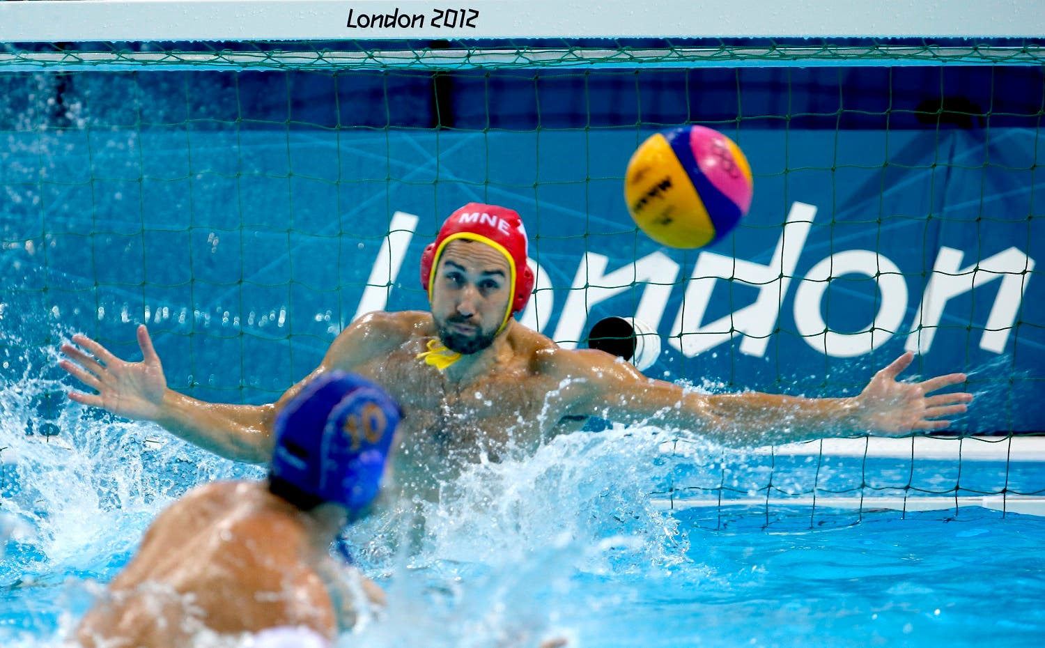 Serbia's Filip Filipovic, bottom, scores on a penalty against Montenegro goalkeeper Milos Scepanovic during the men's water polo bronze medal match at the 2012 Summer Olympics, Sunday, Aug. 12, 2012, in London. (AP