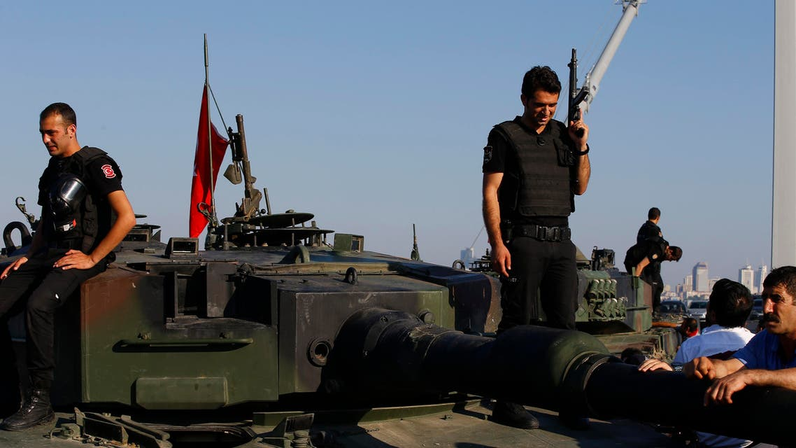 Turkish police officers, stand atop tanks abandoned by Turkish army officers, near Istanbul's Bosphorus Bridge