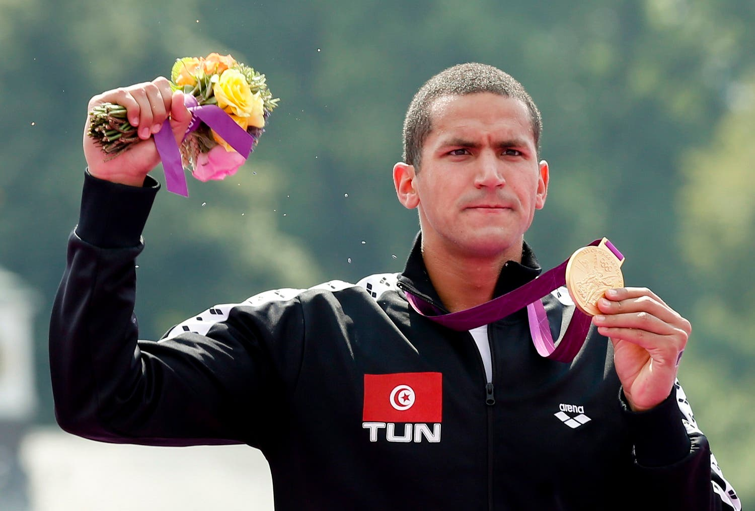 Tunisia's Oussama Mellouli poses with his gold medal after the men's 10km marathon swimming at Hyde Park during the London Olympic Games August 10, 2012. (Reuters)